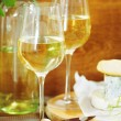 Still life with glasses of white wine and chesse - Stock Photo