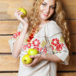 Woman in traditional dress holding apples in her hands — Stockfoto