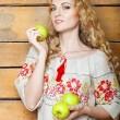 mujer con vestido tradicional sosteniendo manzanas en sus manos — Foto de Stock