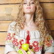 Woman in traditional dress holding apples in her hands — Stock Photo #23497039