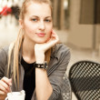 Smiling woman drinking coffee smiling at camera — Stock Photo