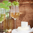 Glasses of white wine, bottle and cheese — Stock Photo