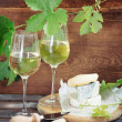 Glasses of white wine, bottle and cheese - Stock Photo