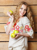 Woman in traditional dress holding apples in her hands — Stock Photo