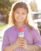 Smilling girl holding ice cream cone in her hands outdoors — Stock Photo