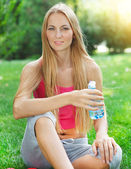 Woman drinking water after fitness exercise — Stock Photo