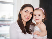 Happy smiling mother with baby girl indoor — Stock Photo