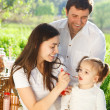 Happy young family with baby girl on a picnic — Stock Photo