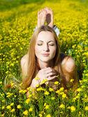 Genç güzel sarışın kız papatya çiçekleri alan üzerinde döşeme — Stok fotoğraf