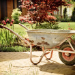 Retro wheelbarrow stored in garden — Stock Photo #26871711