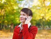 Leende kvinna talar i mobiltelefon — Stockfoto