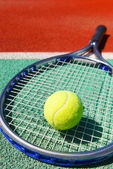 Tennis racquet and ball on the clay tennis court — Stock Photo
