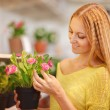 Young woman buying flowers at a garden center — Stock Photo #28043143