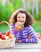 Smiling little girl with basket of red apples — Stock Photo
