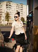 Young beautiful smiling woman fills petrol car — Stock Photo