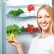 Beautiful young woman near refrigerator — Stock Photo