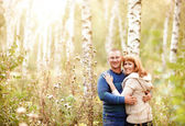 Happy smiling couple in the autumn forest — Stock Photo