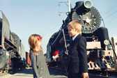 Little boy and little girl near the trains — Stock Photo