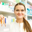 Closeup of a female pharmacist holding packet at drugstore — Stock Photo