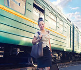 Woman with a suitcase standing on the platform — Stock Photo