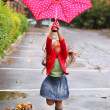 Child with polka dots umbrella wearing red rain boots — Stock Photo