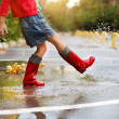 Child wearing red rain boots jumping into a puddle — Stock Photo #30328233