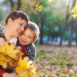 Mother and her son in a autumn park — Stock Photo