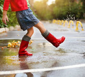 Child wearing red rain boots jumping into a puddle — Stock Photo