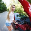 Woman standing near the opened hood of the broken cabriolet — Stock Photo