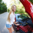 Woman standing near the opened hood of the broken cabriolet — Stockfoto