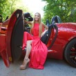 Young woman in red dress siting in a  sports car — Stock Photo