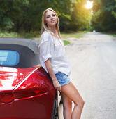 Bir spor arabanın yakınında duran genç kadın — Stok fotoğraf