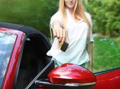 Happy young woman holding keys to her cabrio — Stock Photo
