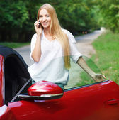 Young woman standing near a sports car and talking by mobile ph — Stock Photo