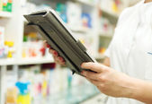 Pharmacist working with a tablet pc in the pharmacy — Stock Photo