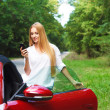 Beautiful blond young woman in a sports car — Stock Photo