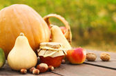 Pumpkins, jam, nuts and basket with apples — Stock Photo