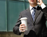 Close up of the hands of the businessman with a mobile phone and — Stock Photo