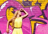 Giovane ragazza bionda attraente vicino al muro con graffiti — Foto Stock