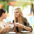 young women drinking coffee in a cafe outdoors — Stock Photo