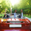 Happy free couple driving in red retro car cheering joyful with — Stock Photo #31855525