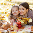 Stock Photo: Happy young mother with daughter in autumn park