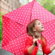Little girl with polka dots umbrella under the rain — Stock Photo