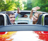 Couple in red cabriolet in a sunny day — Stock Photo