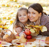 Happy young mother with daughter in autumn park — Stock Photo