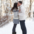 Happy young couple having fun in the winter park — Stock Photo