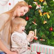 Mother with her little daughter under the Christmas tree — Stock Photo