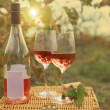Stock Photo: Two glasses and bottle of the rose wine in autumn vineyard.