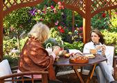 Women drinking coffee in a garden outdoors — Stock Photo