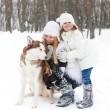 Mother with daughter with huskies dog — Stock Photo